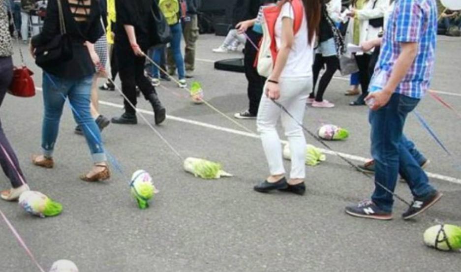 En China, jóvenes pasean lechugas en lugar de perros.