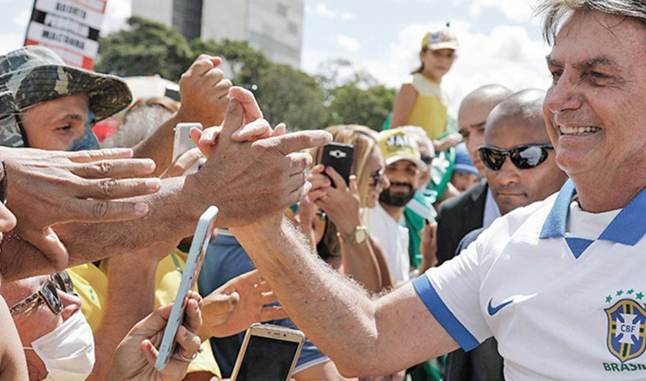 INDIFERENCIA Bolsonaro paseó el fin de semana por la zona residencial de Brasilia y comió un pancho en un carrito instalado en una vereda.