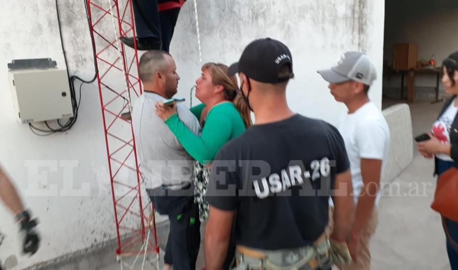 Arias (de gris) descendió tras cinco horas de amenazar con quitarse la vida. En el suelo, fue recibido por familiares.